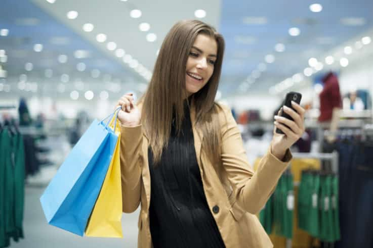 Cheerful female shopper texting on mobile phone